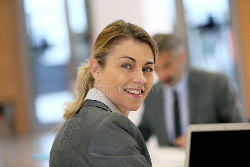 Stående av att le affärskvinnan på bärbara datorn fotografering för bildbyråer