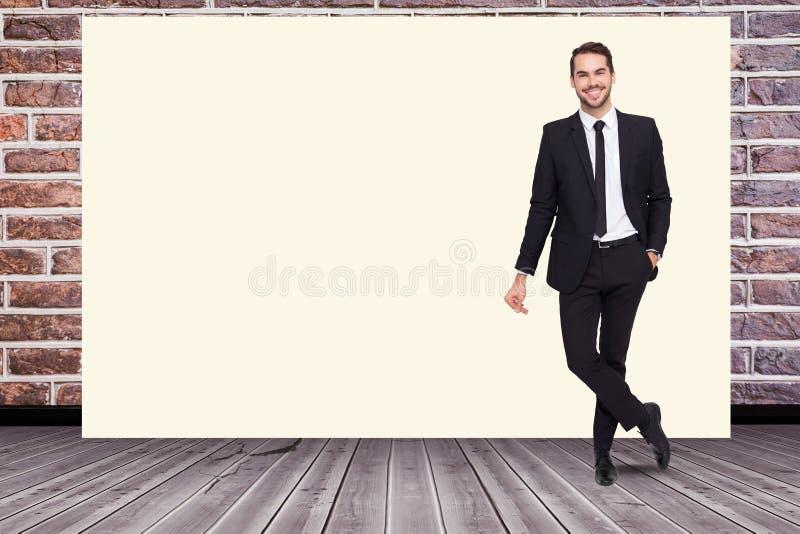 Stående av att le affärsmananseende vid den tomma vita affischtavlan mot tegelstenväggen arkivfoto