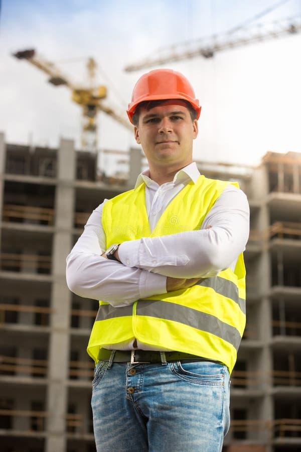 Stående av att le affärsmannen i hardhaten och säkerhetsvästen som poserar mot byggnad under konstruktion arkivfoton