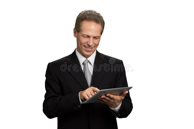 Stående av att le affärsmannen som arbetar på minnestavlan royaltyfri foto