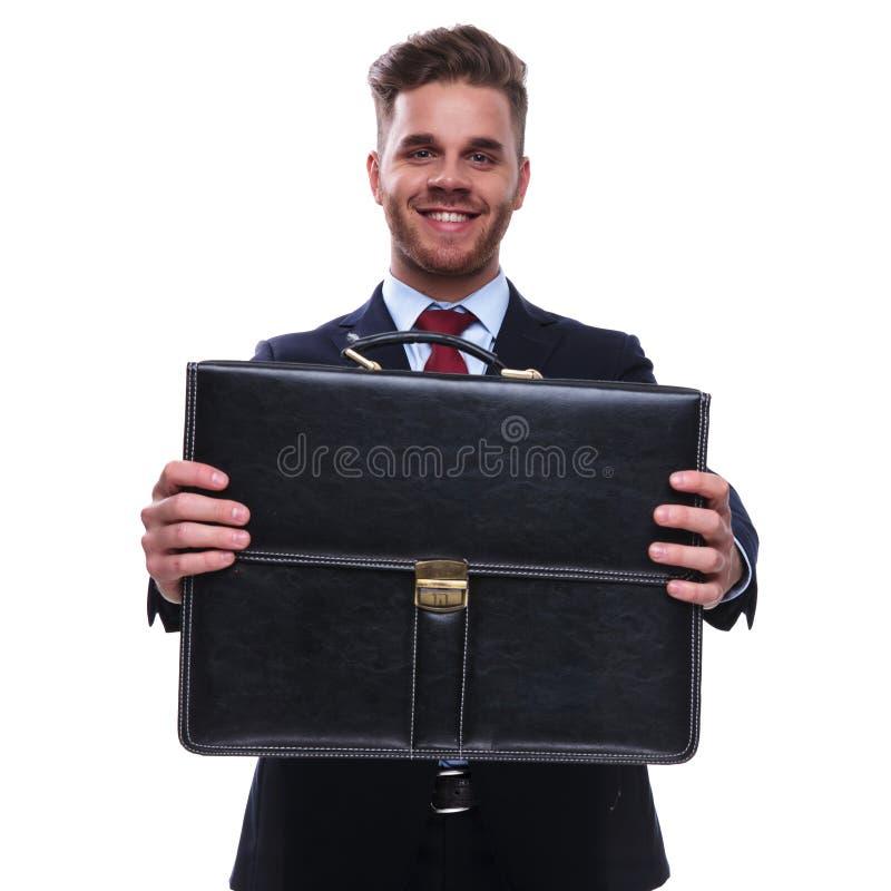 Stående av att le affärsmannen som erbjuder dig hans fall royaltyfria foton