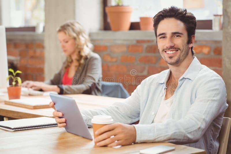 Stående av att le affärsmannen som i regeringsställning rymmer den digitalt minnestavlan och kaffe royaltyfri bild