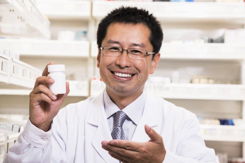 Stående av att le apotekaren som rymmer en receptläkarbehandlingflaska i hans hand fotografering för bildbyråer