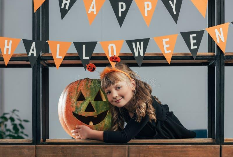 stående av att le barnet i den halloween dräkten på sniden pumpa och att hänga flaggor fotografering för bildbyråer