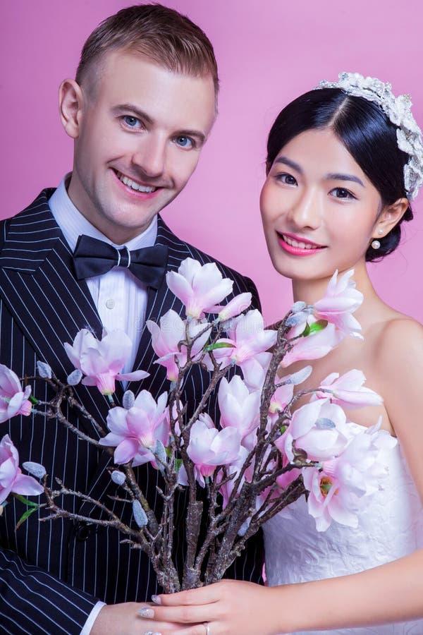 Download Stående Av Att Le Brölloppar Som Rymmer Konstgjorda Blommor Mot Rosa Bakgrund Fotografering för Bildbyråer - Bild av stiligt, kulört: 78731889