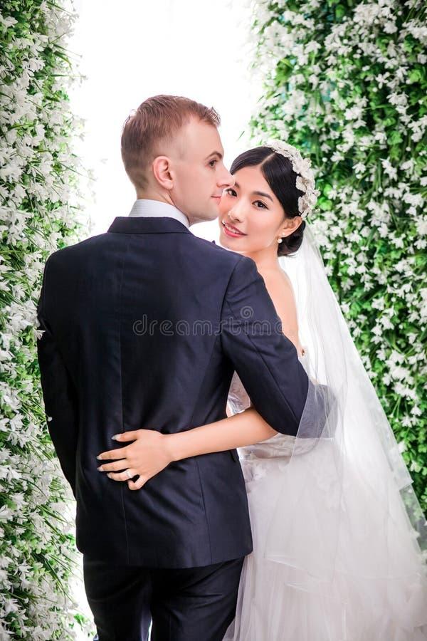 Download Stående Av Att Le Brudanseende Med Brudgummen Mot Blommagarneringar Arkivfoto - Bild av tänt, livstid: 78732396