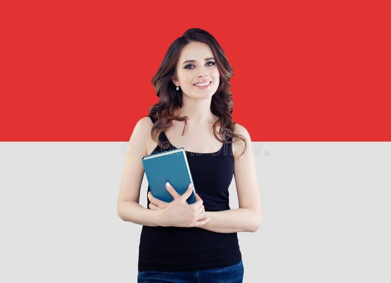 Stående av att le brunettkvinnan med den Monaco flaggan arkivfoto