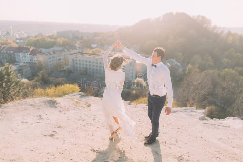 Stående av att le dansbrölloppar på den bästa kulle-, stads- och himmelbakgrunden royaltyfri foto