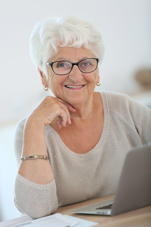 Stående av att le den äldre kvinnan med bärbara datorn arkivfoton