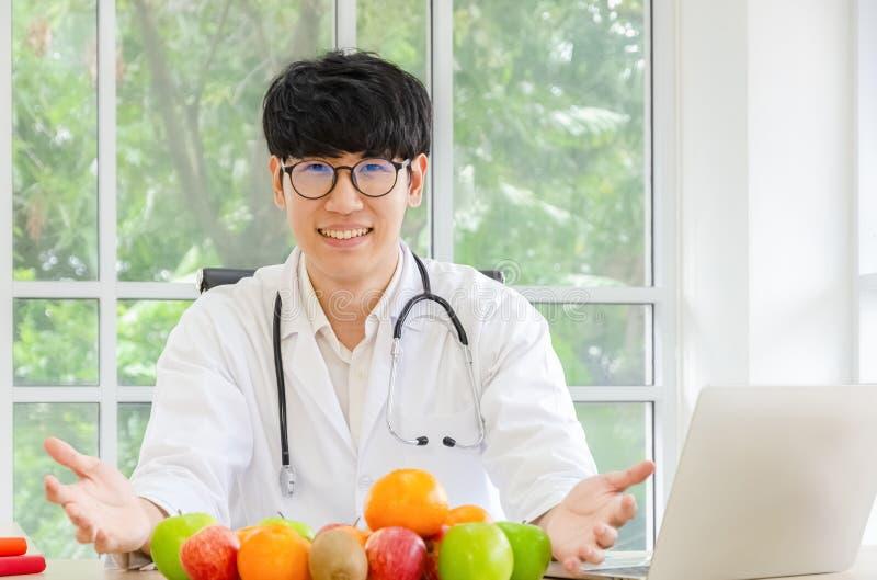 Stående av att le den asiatiska manliga näringsfysiologen med sunda nya organiska frukter i hans kontor, sjukvård och att banta b arkivbild
