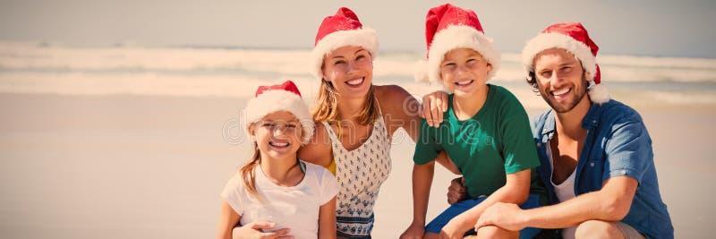Stående av att le den bärande jultomtenhatten för familj på stranden arkivbild