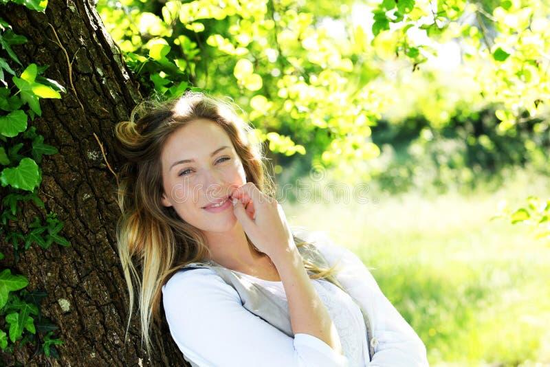 Stående av att le den blonda kvinnan i skog royaltyfria foton