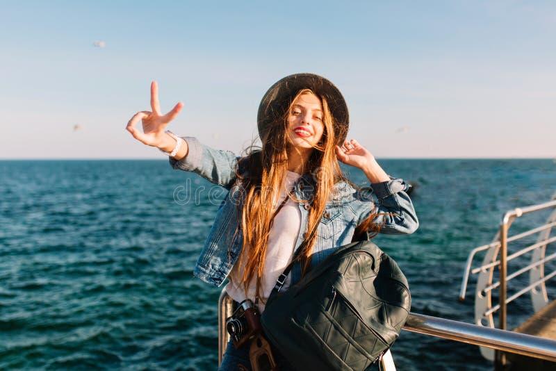 Stående av att le den gladlynta brunettflickan i den moderiktiga hatten som framme poserar av havet med fredtecknet Förtjusande l royaltyfri bild