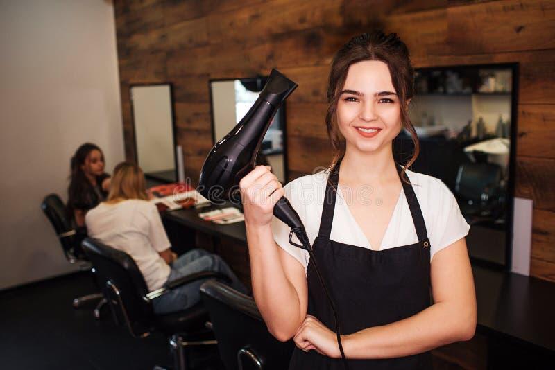 Stående av att le den härliga kvinnafrisören som ser kameran, medan rymma den yrkesmässiga hårtorken på salong arkivbild