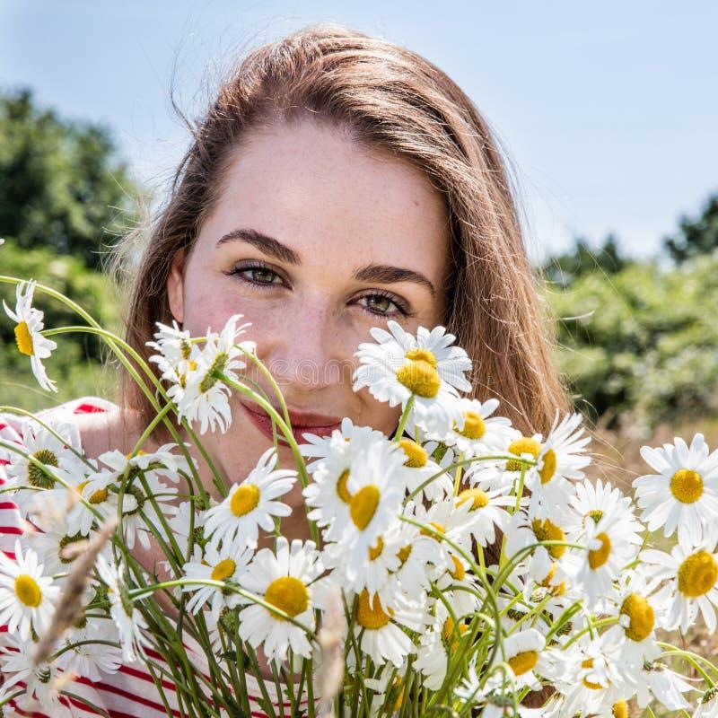 Stående av att le den härliga unga kvinnan med tusenskönablommabuketten fotografering för bildbyråer
