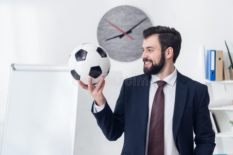 stående av att le den hållande fotbollbollen för affärsman royaltyfri foto