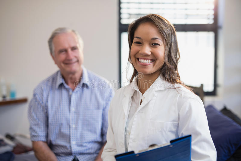 Stående av att le den hållande mappen för kvinnlig terapeut med den höga manliga patienten royaltyfri foto