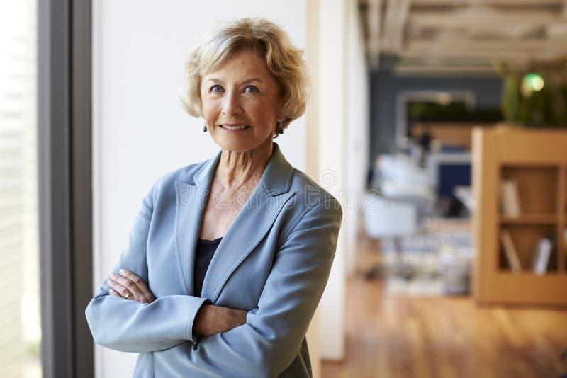 Stående av att le den höga affärskvinnan In Modern Office som står vid fönstret arkivbild