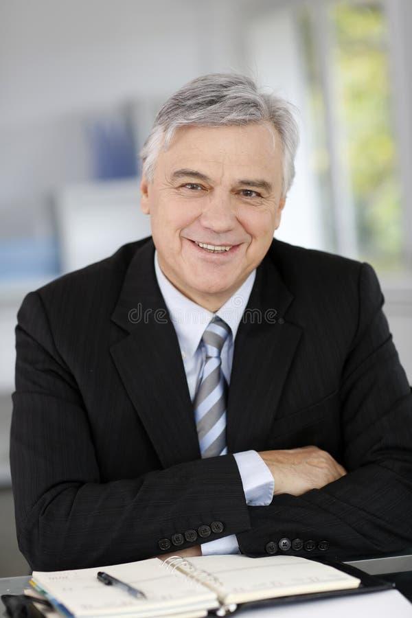 Stående av att le den höga affärsmannen på kontoret fotografering för bildbyråer