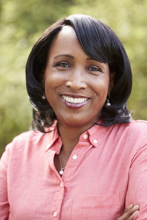 Stående av att le den höga afrikansk amerikankvinnan, lodlinje arkivfoton