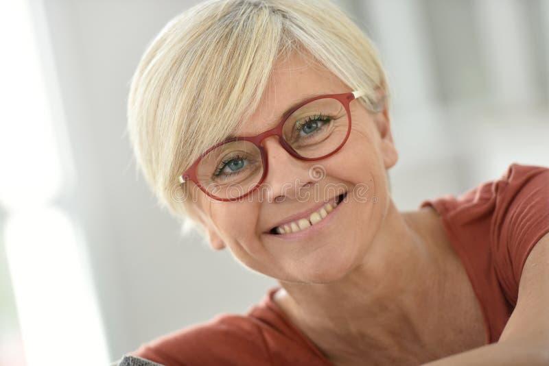 Stående av att le den höga damen med glasögon fotografering för bildbyråer