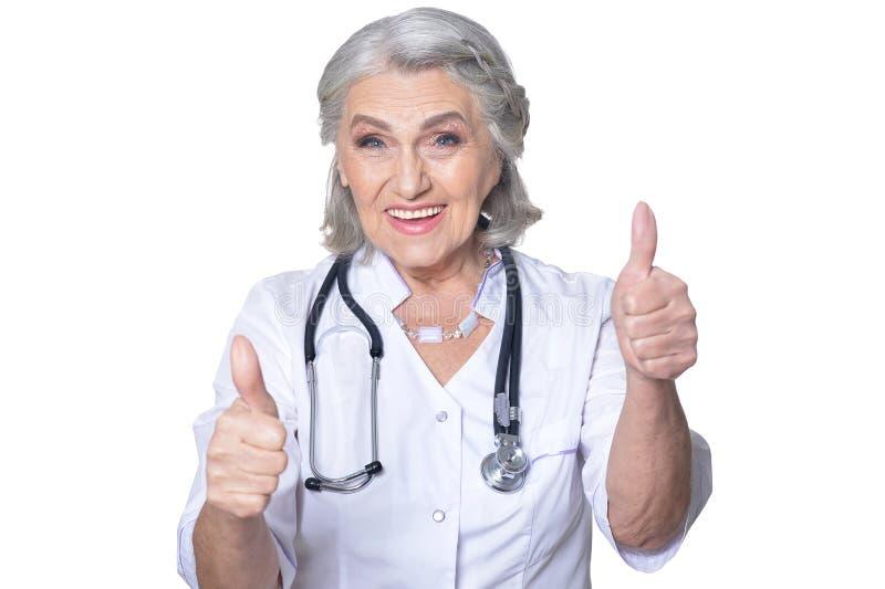 Stående av att le den höga doktorn som visar tummar upp på vit bakgrund royaltyfri foto