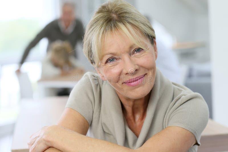 Stående av att le den höga kvinnan med folk i baksidan arkivbilder