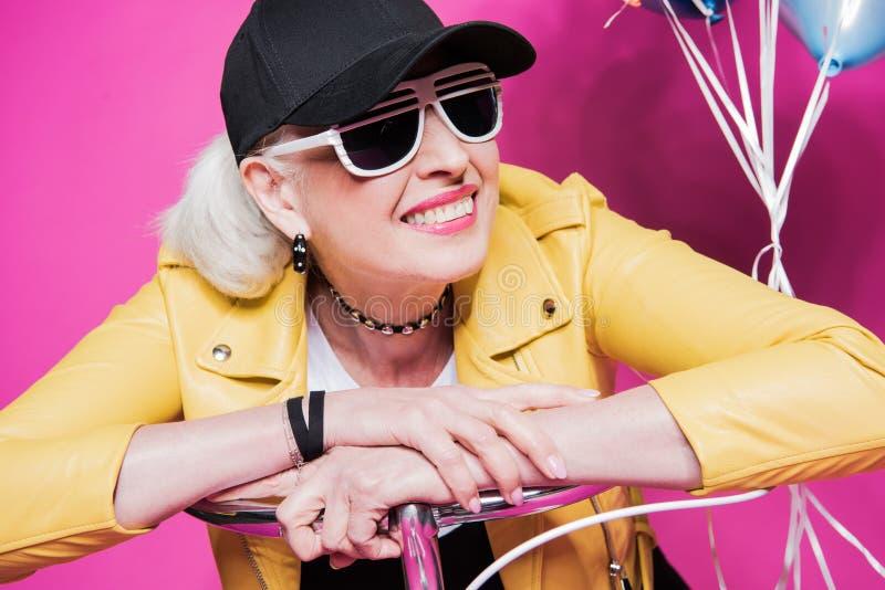 Stående av att le den höga kvinnan som bär det gula läderomslaget och sunglesses royaltyfria foton