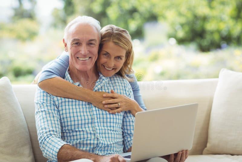 Stående av att le den höga kvinnan som omfamnar en man i vardagsrum, medan genom att använda bärbara datorn royaltyfri fotografi