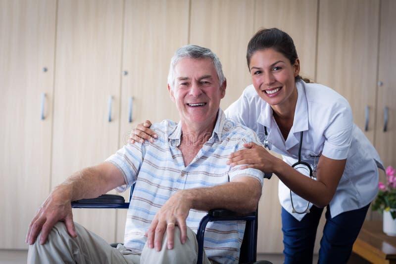 Stående av att le den höga mannen och den kvinnliga doktorn i vardagsrum fotografering för bildbyråer