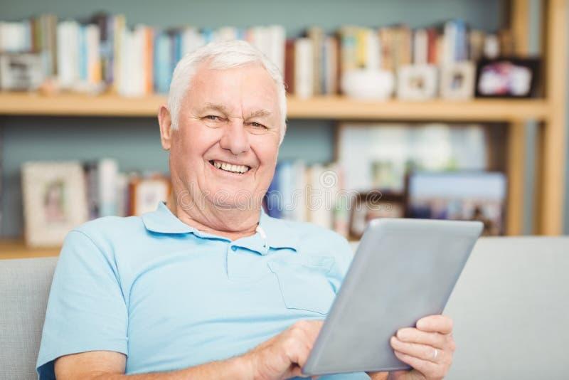 Stående av att le den höga mannen som använder den digitala minnestavlan royaltyfri foto