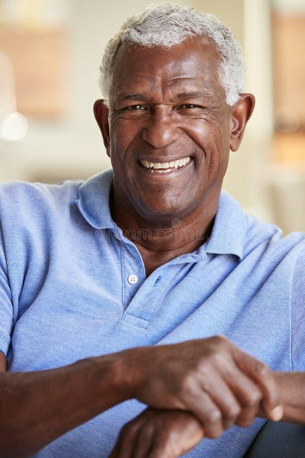 Stående av att le den höga mannen som kopplar av på Sofa At Home royaltyfria foton