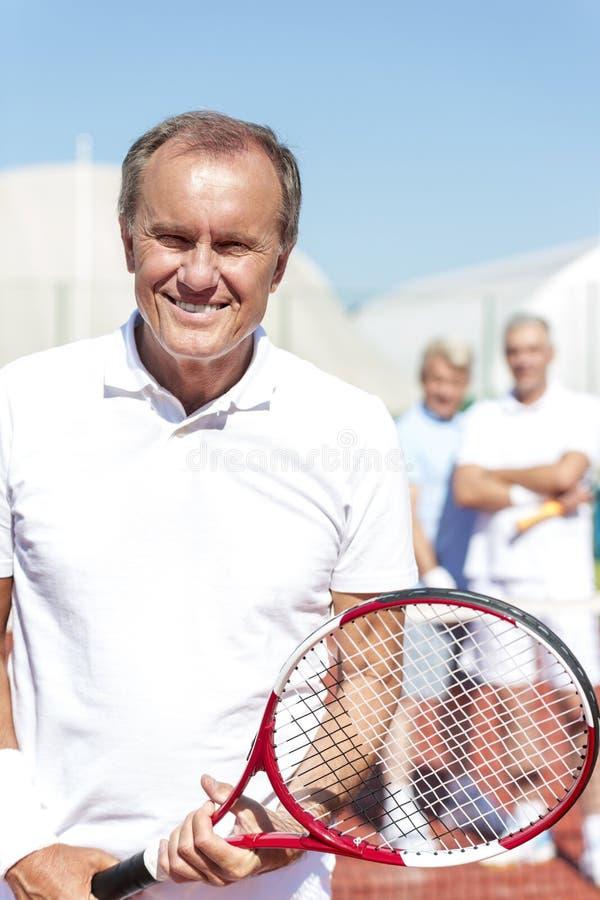Stående av att le den höga mannen som rymmer tennisracket, medan stå mot mogna vänner på domstolen under solig dag arkivbild