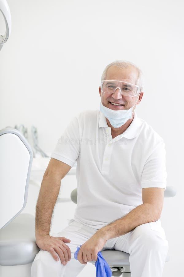 Stående av att le den höga tandläkaren som sitter på stol på den tand- kliniken royaltyfri foto