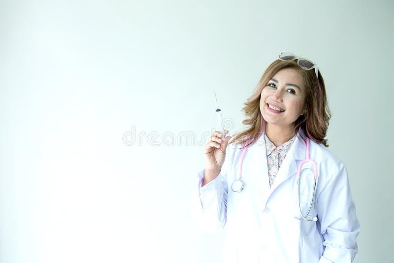 Stående av att le den kvinnliga doktorn med injektionvisaren Friendl royaltyfri foto