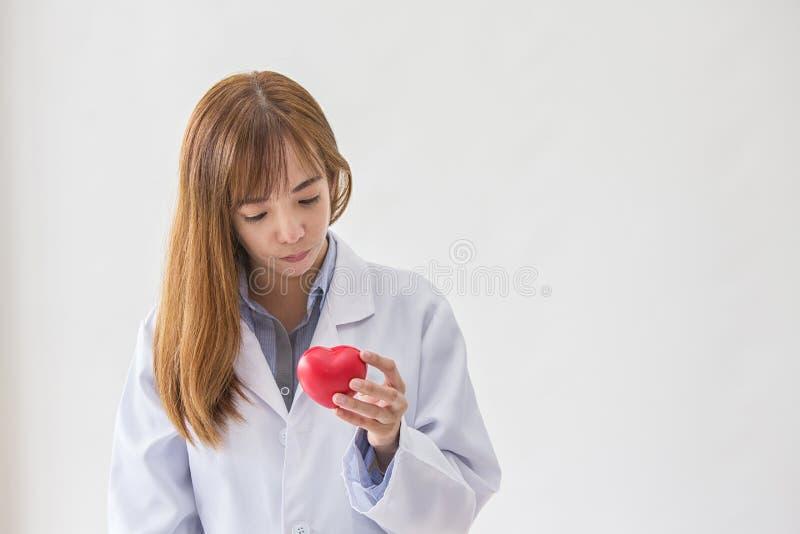 Stående av att le den kvinnliga doktorn med röd hjärta Vänlig doktor för ung kvinna med röd hjärta förestående askfat royaltyfria bilder