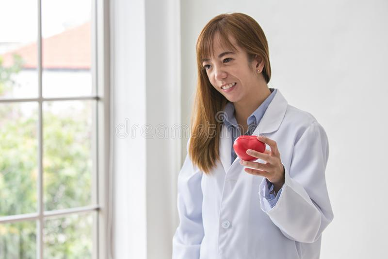 Stående av att le den kvinnliga doktorn med röd hjärta Vänlig doktor för ung kvinna med röd hjärta förestående Selektivt fokusera arkivfoto