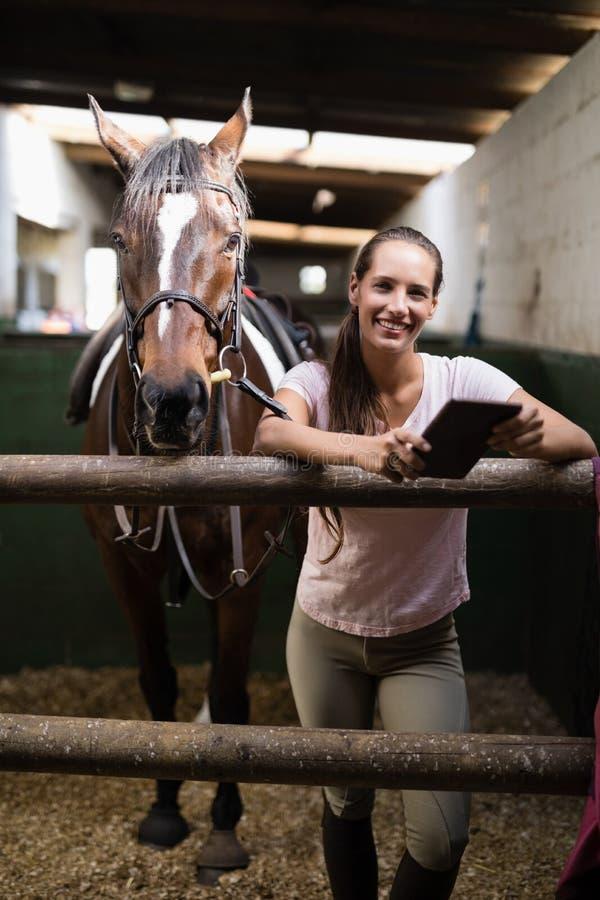 Stående av att le den kvinnliga jockeyn som använder den digitala minnestavlan, genom att stå vid hästen royaltyfri foto