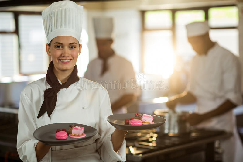 Stående av att le den kvinnliga kocken som framlägger efterrättplattor fotografering för bildbyråer