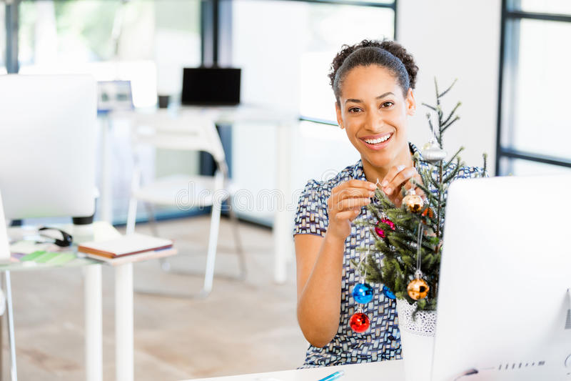 Stående av att le den kvinnliga kontorsarbetaren med julgranen arkivfoton