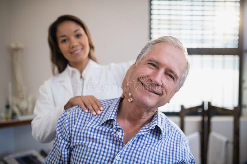 Stående av att le den kvinnliga terapeuten som masserar halsen royaltyfri foto