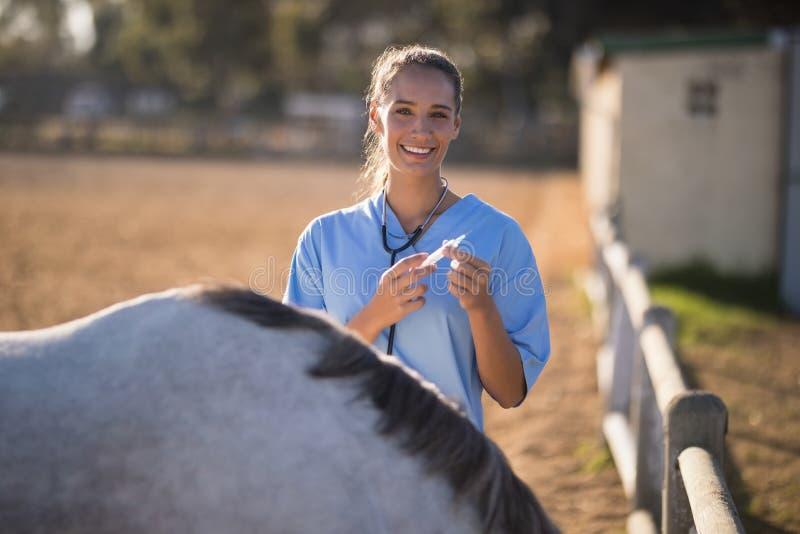 Stående av att le den kvinnliga veterinärinnehavinjektionssprutan royaltyfri fotografi