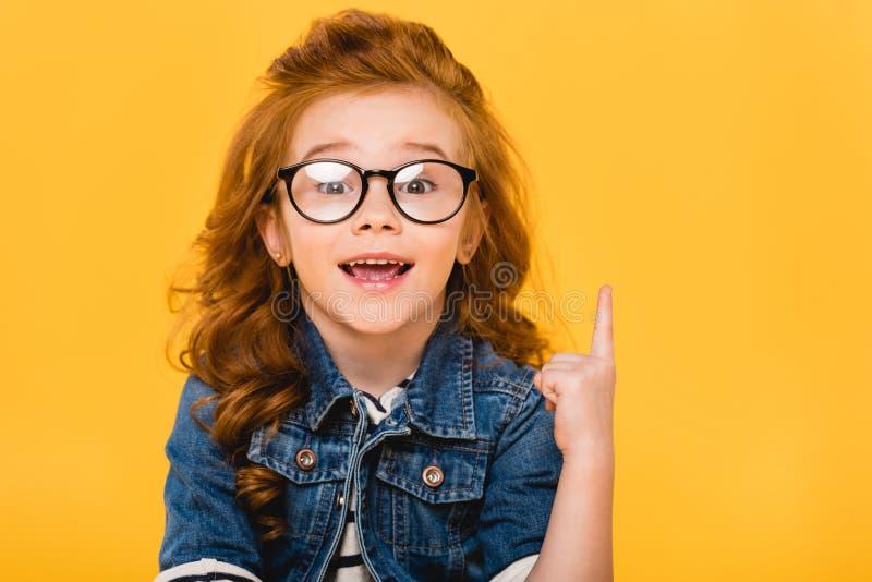 stående av att le den lilla ungen i glasögon som pekar upp fotografering för bildbyråer
