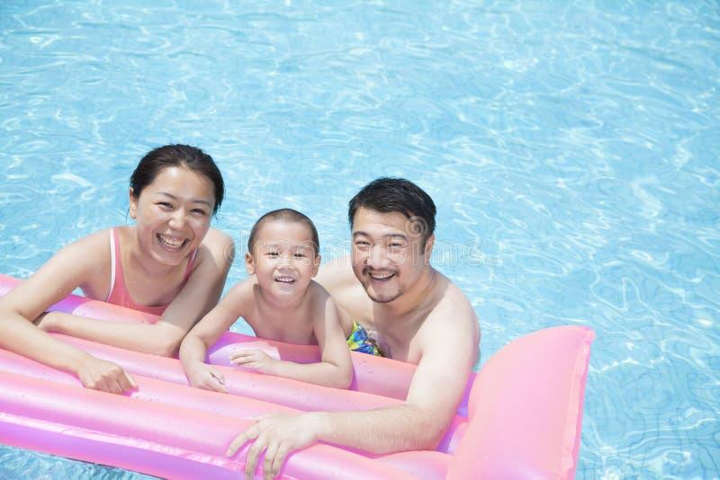 Stående av att le den lyckliga familjen som svävar i pölen på en uppblåsbar flotte arkivbilder