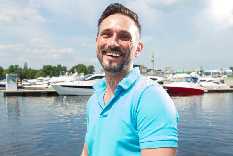 Stående av att le den lyckliga kappseglaren på marina med fartygbakgrund Tid för segling för sommarsemester för den manliga livss arkivbild