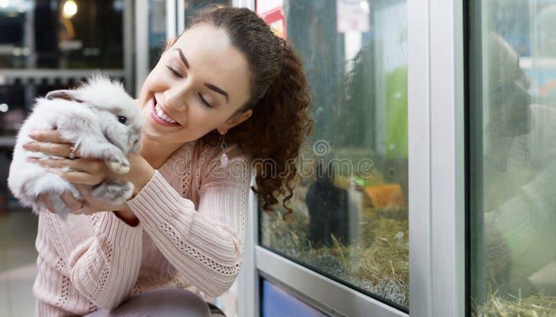 Stående av att le den lyckliga kvinnan som rymmer det fluffiga djuret royaltyfria bilder