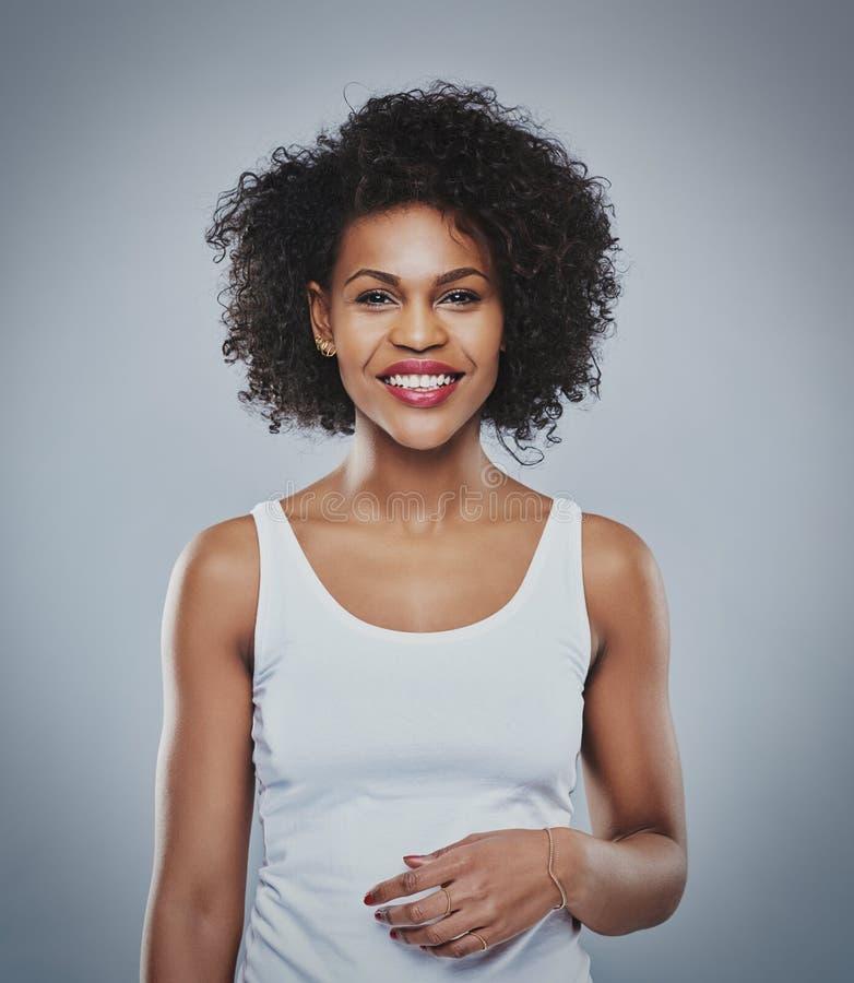 Stående av att le den lyckliga kvinnan, svart kvinna på grå bakgrund arkivbilder
