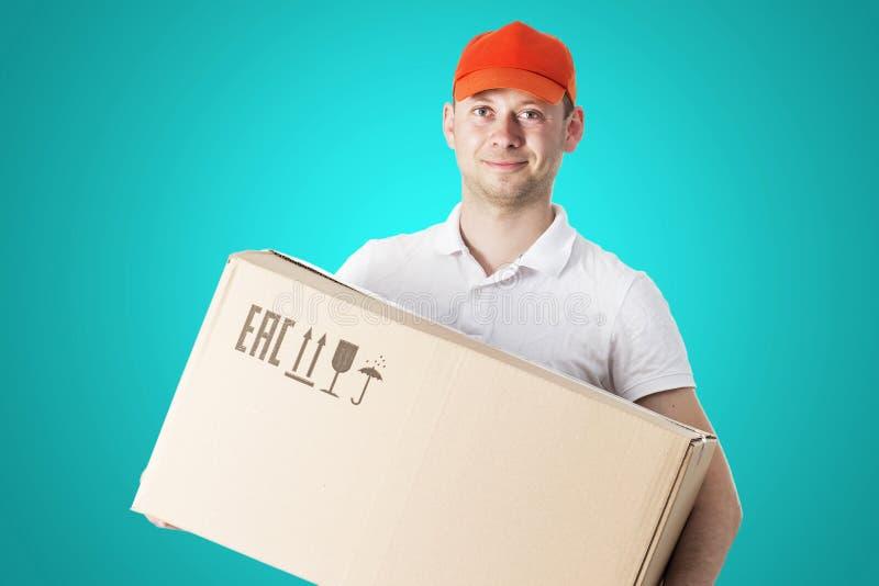 Stående av att le den manliga kuriren i orange lock med kartongen i händer på blå bakgrund Leveranskurirbegrepp arkivfoto