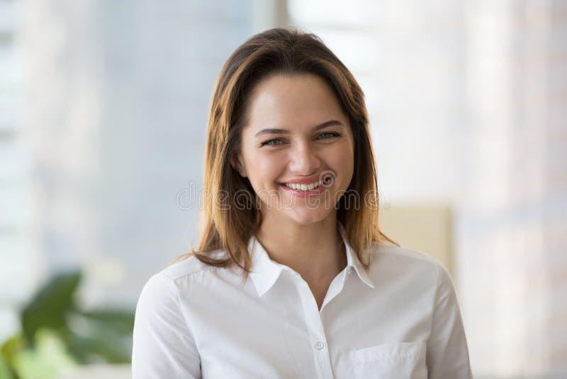 Stående av att le den millennial kvinnan som poserar för företagsbild royaltyfri fotografi
