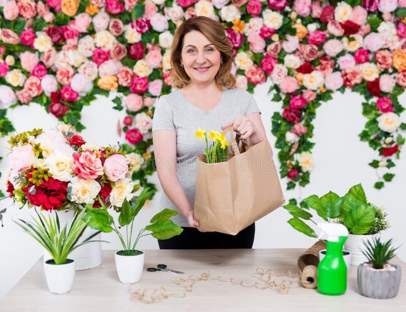 Stående av att le den mogna kvinnablomsterhandlaren eller trädgårdsmästaren som arbetar i blomsterhandel royaltyfria bilder